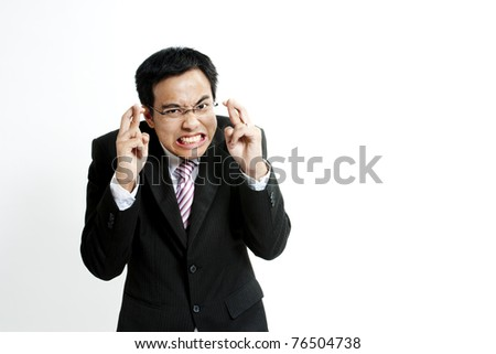 Superstitious - entrepreneur with crossed fingers over white background - stock photo