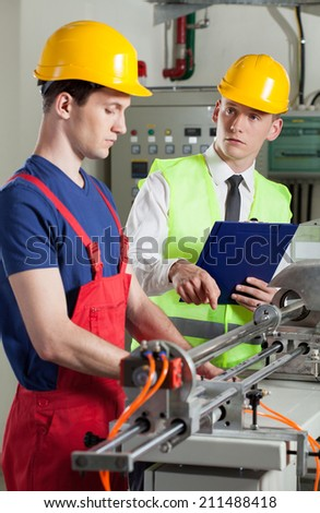Supervisor and machine operator during control, vertical - stock photo