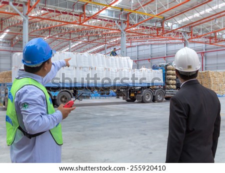 Supervisor and manager checking worker during working in warehouse  - stock photo