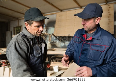 Supervisor and worker to discuss the process of making wood products for furniture. - stock photo