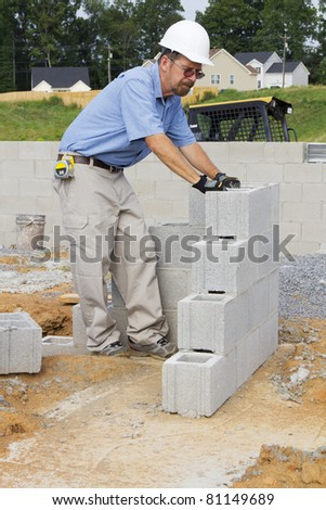 Supervisor checking cinder block where masons started building walls