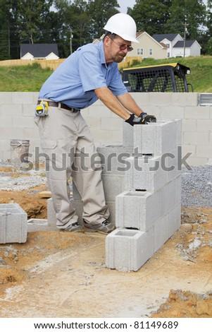 Supervisor checking cinder block where masons started building walls - stock photo