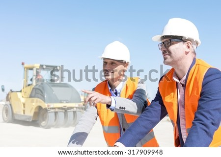 Supervisor explaining plan to colleague at construction site against clear sky - stock photo