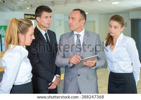 Supervisor with hotel staff, holding tablet - stock photo