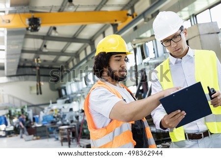 Supervisor with manual worker discussing over clipboard in metal industry