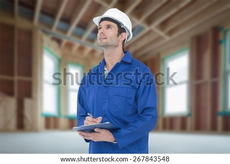 Supervisor writing notes on clip board against house under construction - stock photo