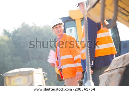 Supervisors discussing at construction site on sunny day - stock photo