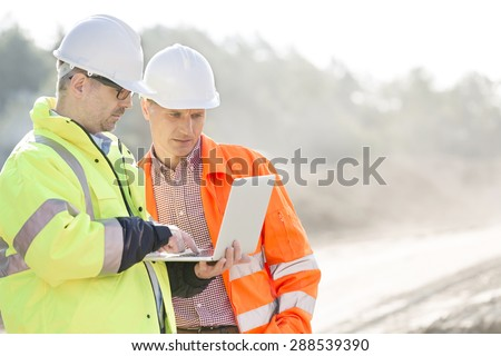 Supervisors using laptop at construction site - stock photo