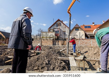 Supervisory controls the building. Main architect engineer is monitoring quality control at construction site. - stock photo