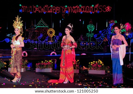 SUPHANBURI,THAILAND-NOVEMBER 28:Thai girls in native dress competition on stage to celebrate the Loy Krathong festival.People float on water a small rafts(Krathong)November 28,2012 in Suphan,Thailand.