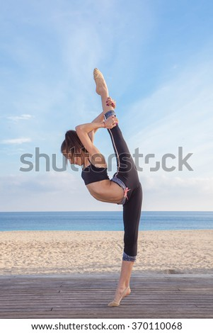 supple flexible gymnast exercising and stretching at the beach - stock photo