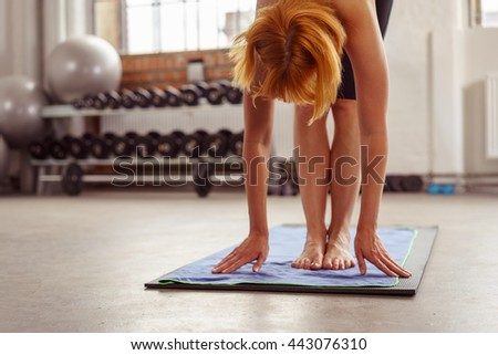 Supple young woman doing bending exercises in a gym bending down with straight legs to touch the floor with her hands, low angle view - stock photo