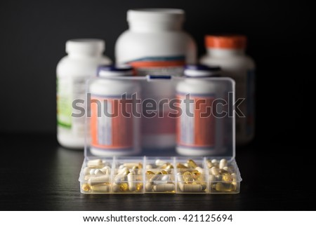 Supplements into daily pill box in front of capsules, pills, softgel and tablet bottles, on black wood table with dark background. Dietary support sort.