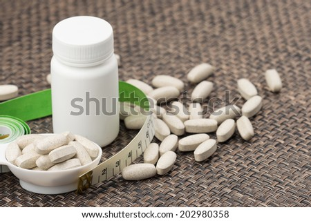 Supplements, medications or vitamins with bottle and spoon - stock photo