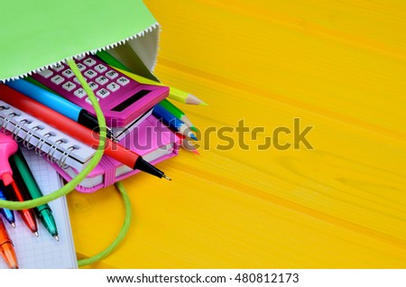 supplies for school in green paper bag on yellow wooden table