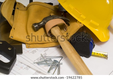 supplies of a construction worker or a handy man, including a hammer, tape measure, nails, tool belt and blue prints or plans - stock photo