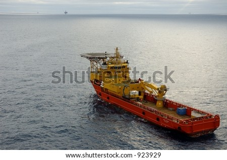 Supply boat with helideck and oil rigs in background