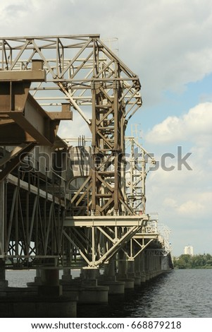 Support above the bridge on the river, steel structure close-up.