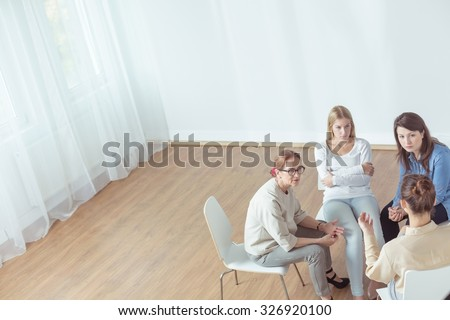 Support group during psychotherapeutic session - horizontal view - stock photo