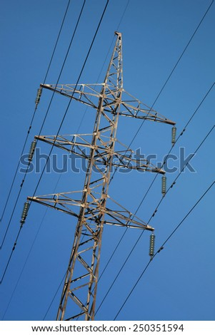 support high voltage against the blue sky above the tops of the forest