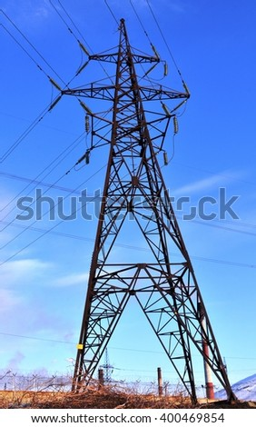 Support high-voltage power lines against the blue spring sky and factory chimneys