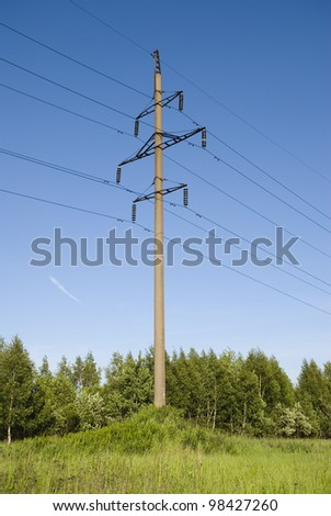 Support of high voltage transmission line is on a green meadow - stock photo