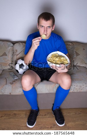 supporter in uniform watching football on tv at home and eating chips - stock photo