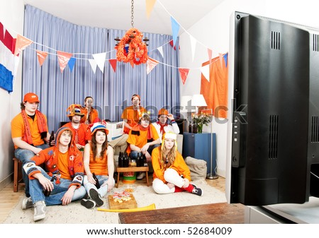 Supporters watching a game at home in front of the television - stock photo