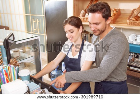 Supporting colleague. Male cafeteria worker showing to his female colleague how to use cash register - stock photo