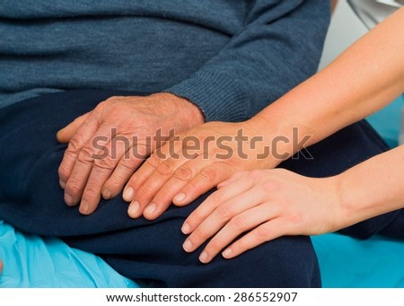 Supporting hands for elderly disabled man with several diseases.