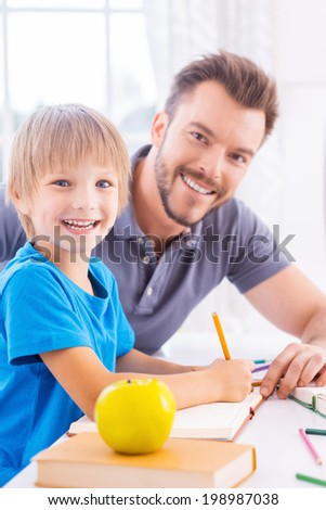 Supporting son in his studying. Side view of cheerful young father helping his son to do homework while both sitting at the table and smiling at camera  - stock photo