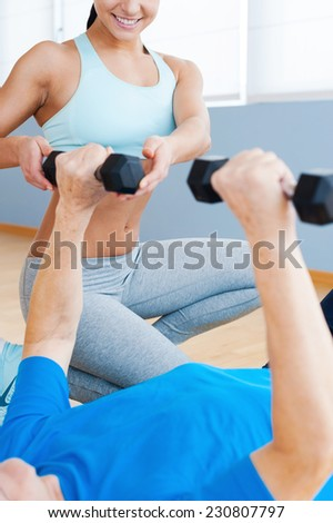 Supporting the all way to recovery. Cropped image of cheerful female personal coach supporting senior man in weight exercises