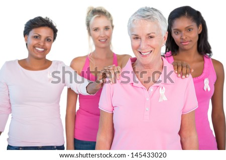 Supportive group of women wearing pink tops and breast cancer ribbons on white background - stock photo