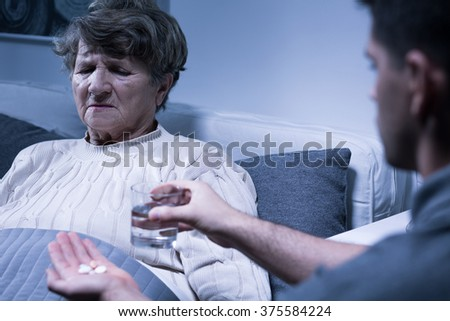 Supportive young grandson giving pills to sick grandmother - stock photo