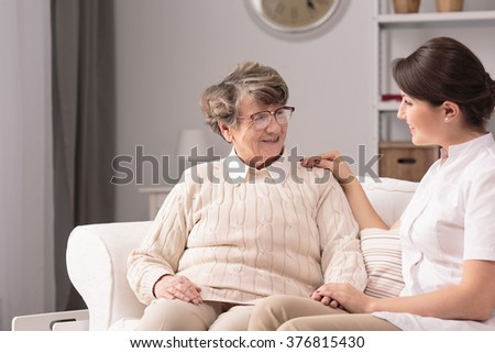 Supportive young woman and older lady at home