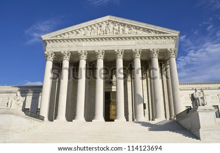 Supreme Court building in Washington, DC with a blue sky background.