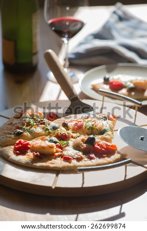 Supreme Pizza with glass of red wine and bottle at home - stock photo