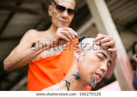 SURATTHANI, THAILAND - MARCH 23 : Thai man during a Buddhist ordination ceremony during which he becomes a monk. Monk shaved his hair and eyebrow on March 23, 2014 in Suratthani, Thailand