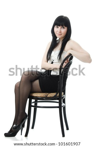 Sure beautiful woman in evening dress sitting on a chair on a white background