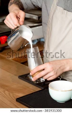 Sure you will love it. Vertical closeup of a barista pouring milk into the glass with coffee - stock photo