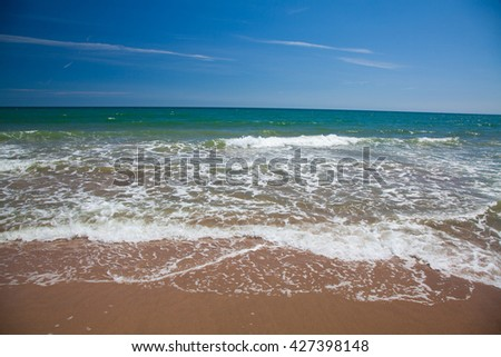 Surf and waves at a beach with blue sky at the mediterranean sea.