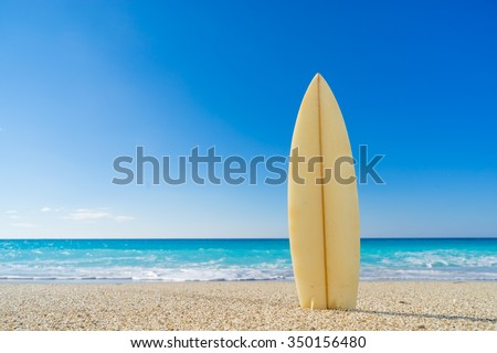 Surf board in the sand at the beach - stock photo