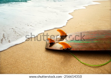 surf board lies on the beach in the waves - stock photo