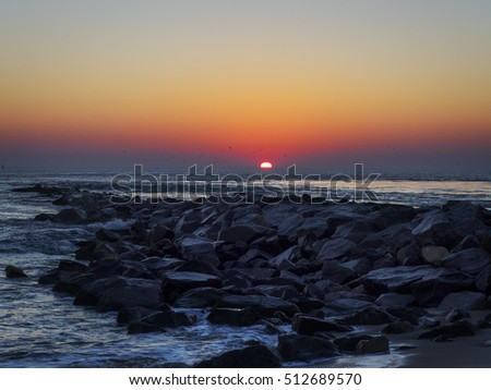 Surf breaking on the rocks of the Indian River, Delaware, jetty at dawn.