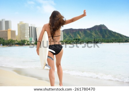 Surf fun - Surfer girl happy carefree going surfing running into water arms up showing success or freedom. Woman with surfboard living healthy active lifestyle in Waikiki beach, Honolulu, Hawaii, USA. - stock photo