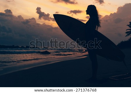 Surf girl at the sunset - stock photo