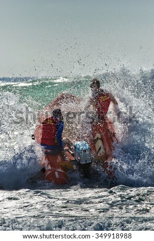 Surf lifesavers power their dinghy through powerful waves at Manly, Sydney. Exciting shot with lots of spray. - stock photo