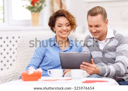 Surf the Internet. Positive delighted young couple holding laptop and sitting at the table while having agreeable time - stock photo