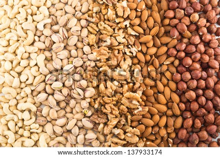 Surface covered with different nut mix of hazelnut, pistachio, peanut, almond, walnut as a food background - stock photo