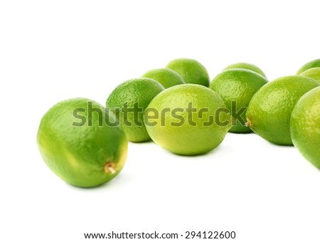Surface covered with multiple ripe green limes, composition isolated over the white background